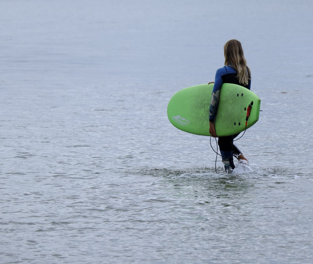 woman walking on body of water carrying green surfboard during daytime