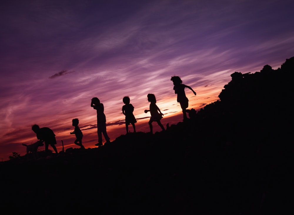 silhouette of children's running on hill