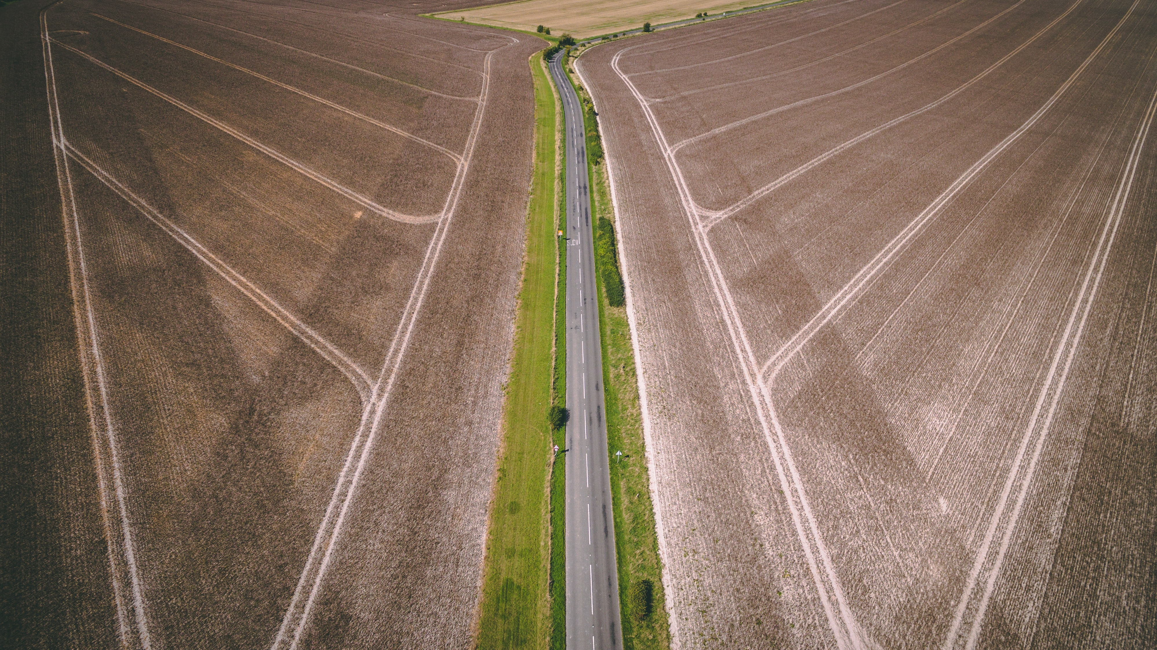 aerial photography of gray concrete road top between brown field during daytime