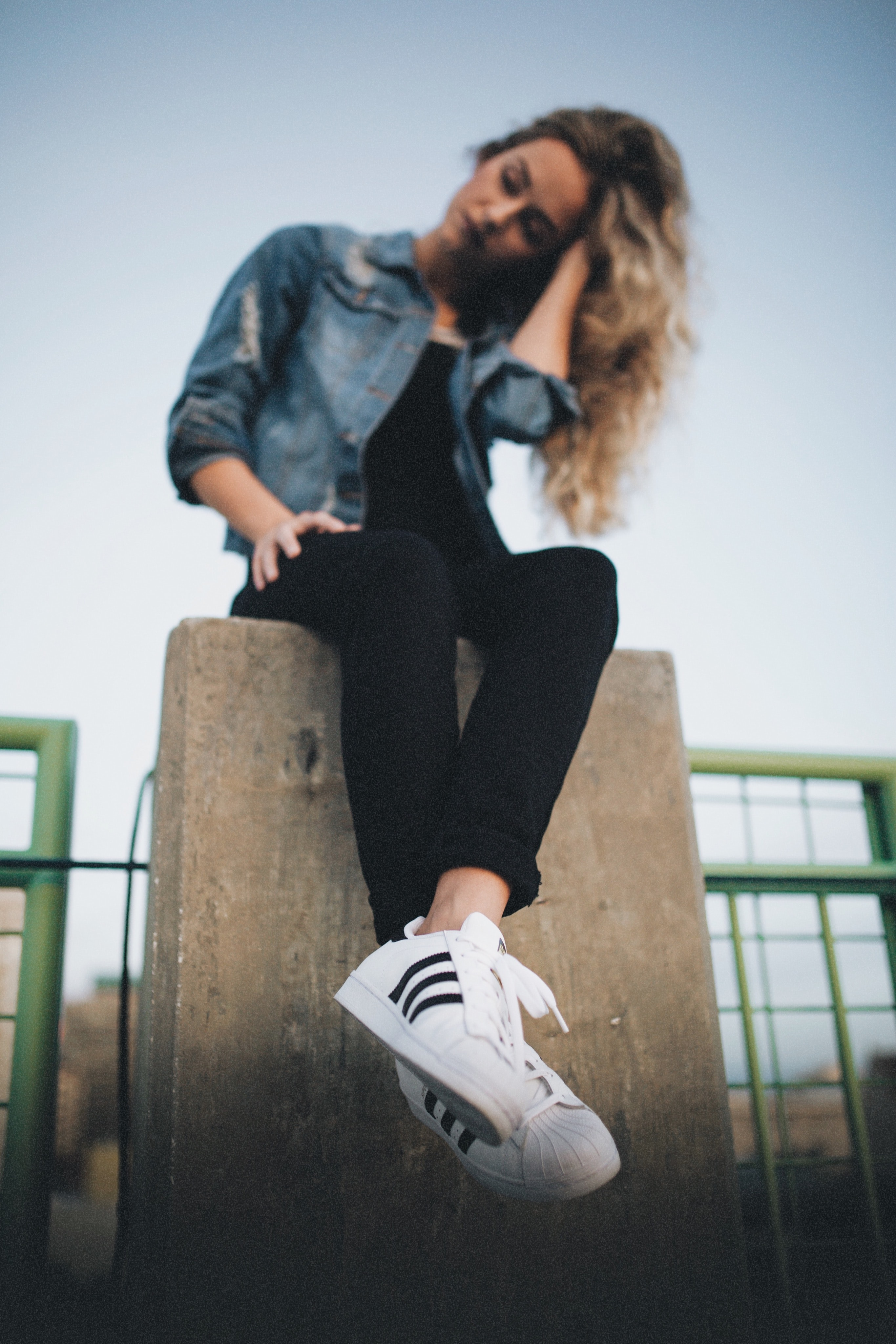 woman in blue denim button-up jacket and black pants sitting on gray concrete post during daytime
