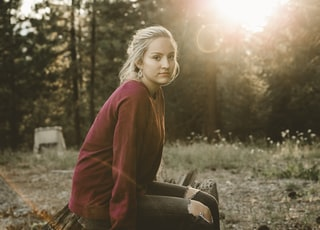 woman in maroon long-sleeved shirt sitting on bench