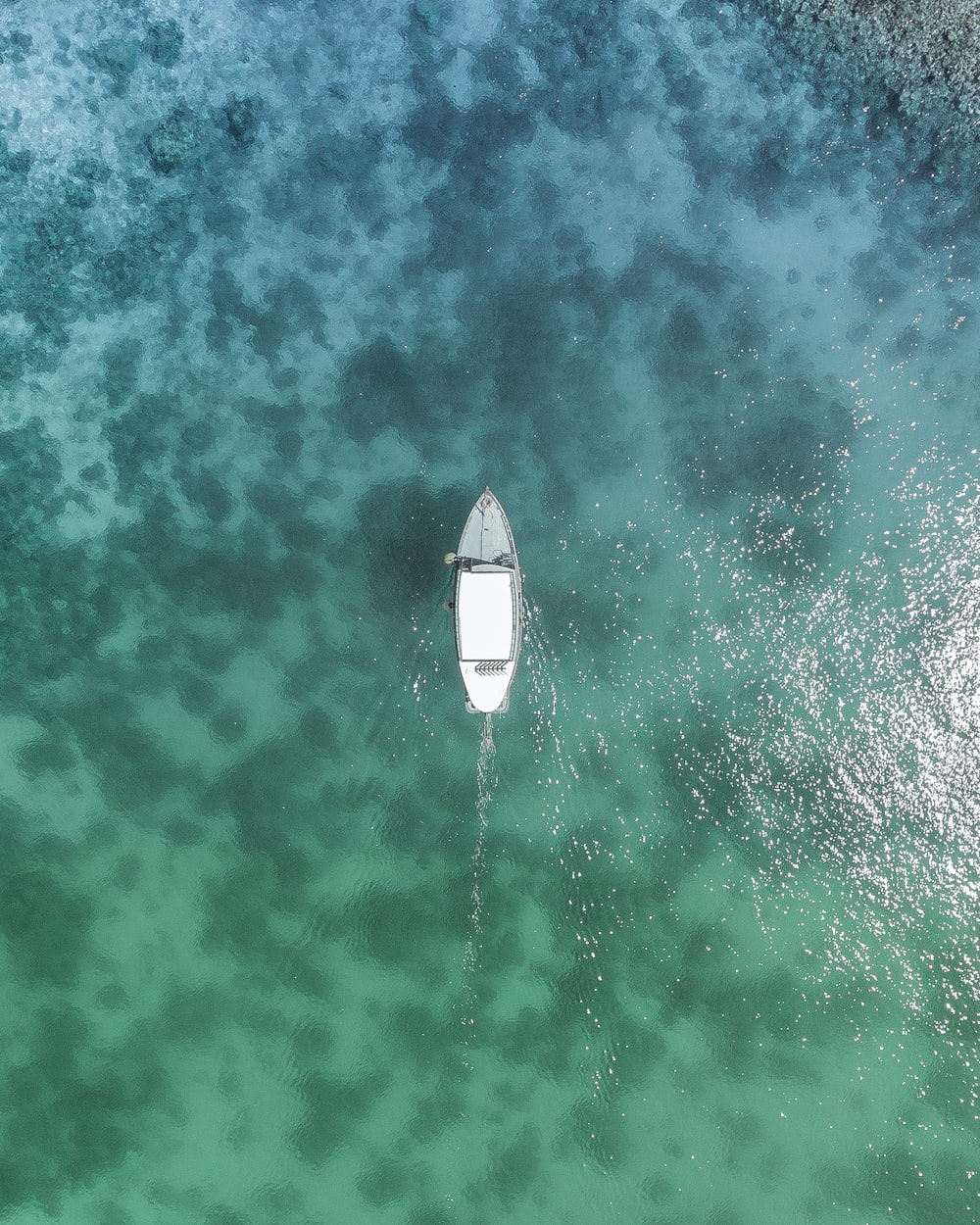 bird's eye view photo of white boat on body of water during daytime