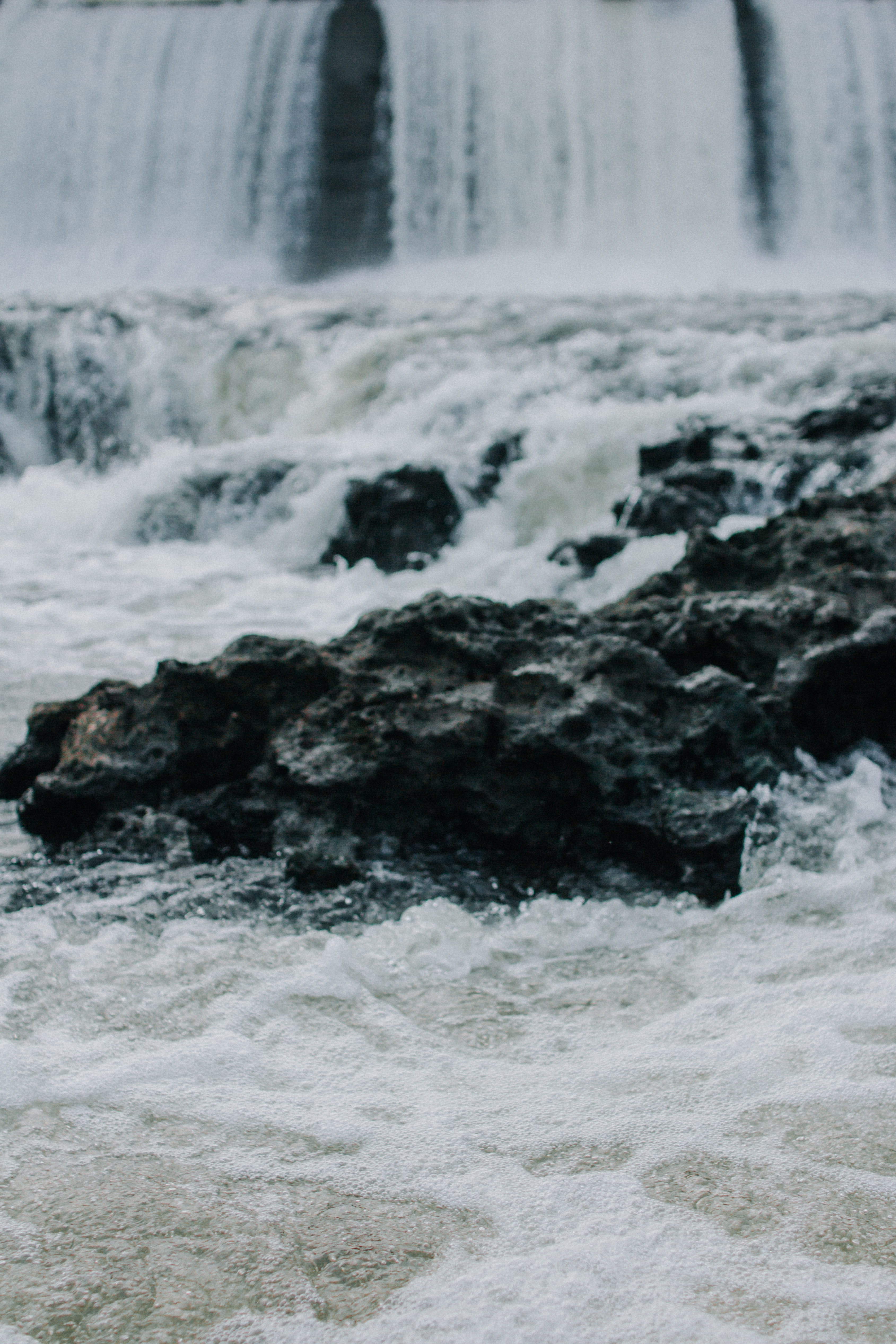 selective focus photography of black rock in waterfalls at daytime