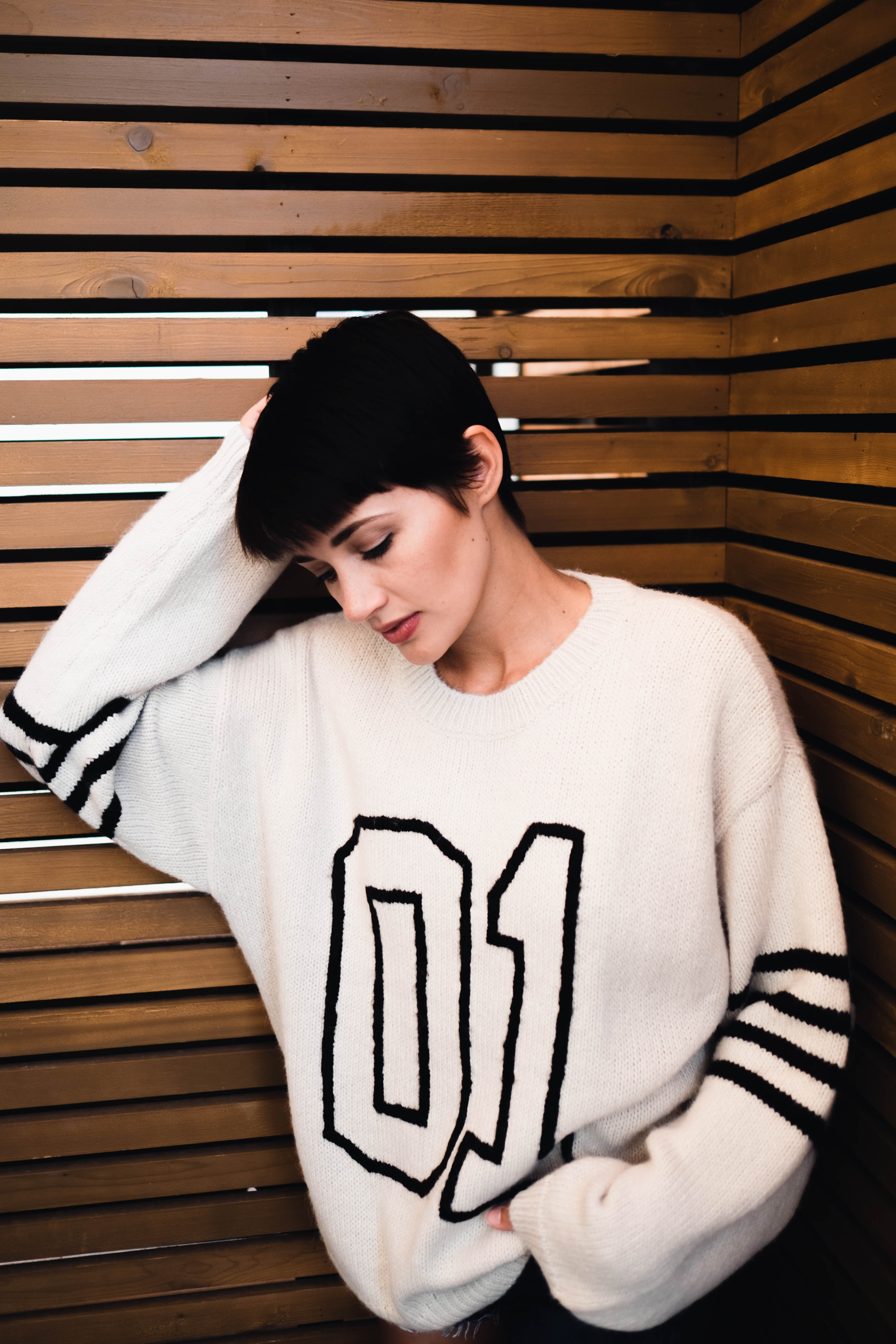 women's wearing black and white sweater near wall