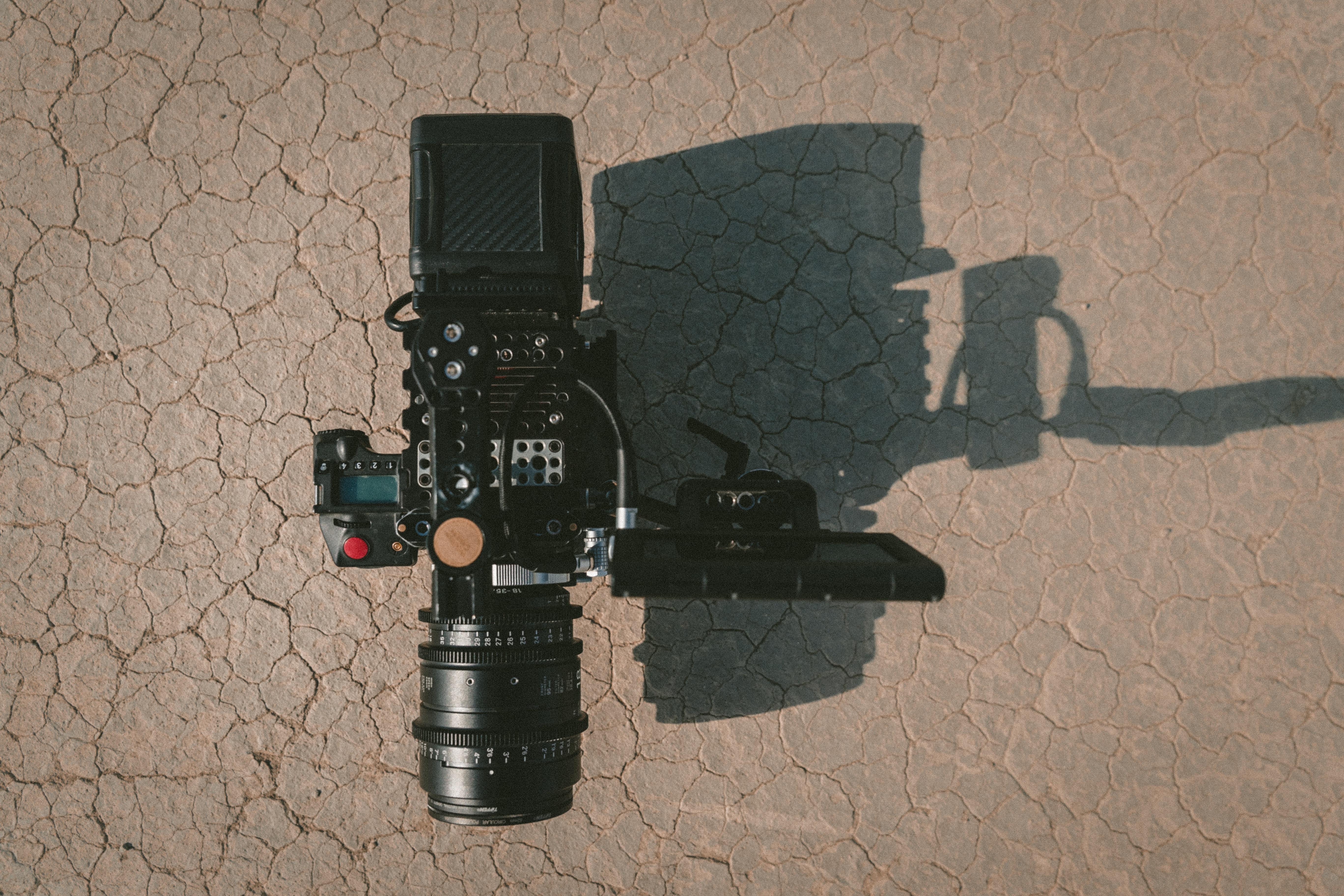 black DSLR camera on brown dirt