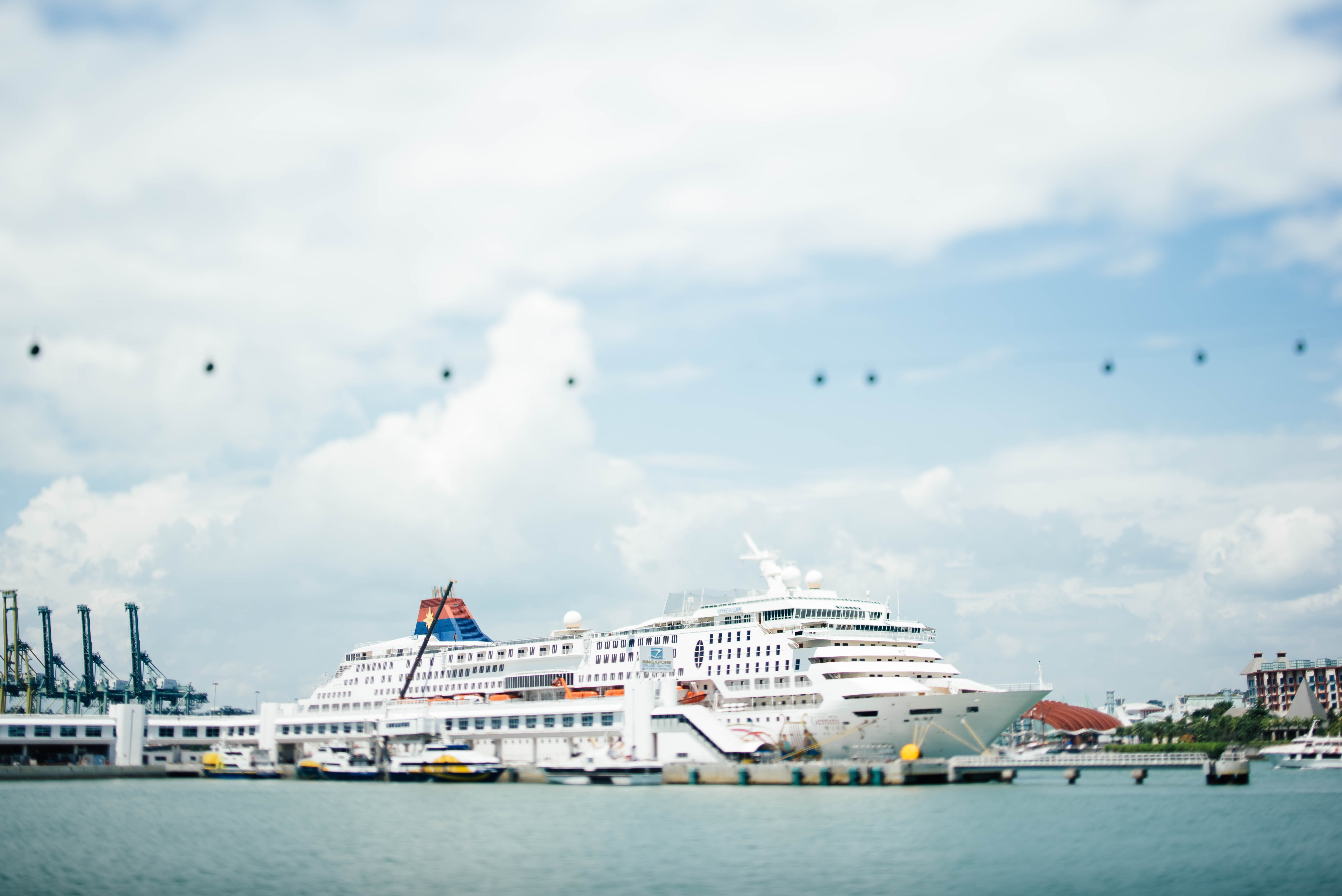 white cruise ship docking on blue bod of water under blue sky