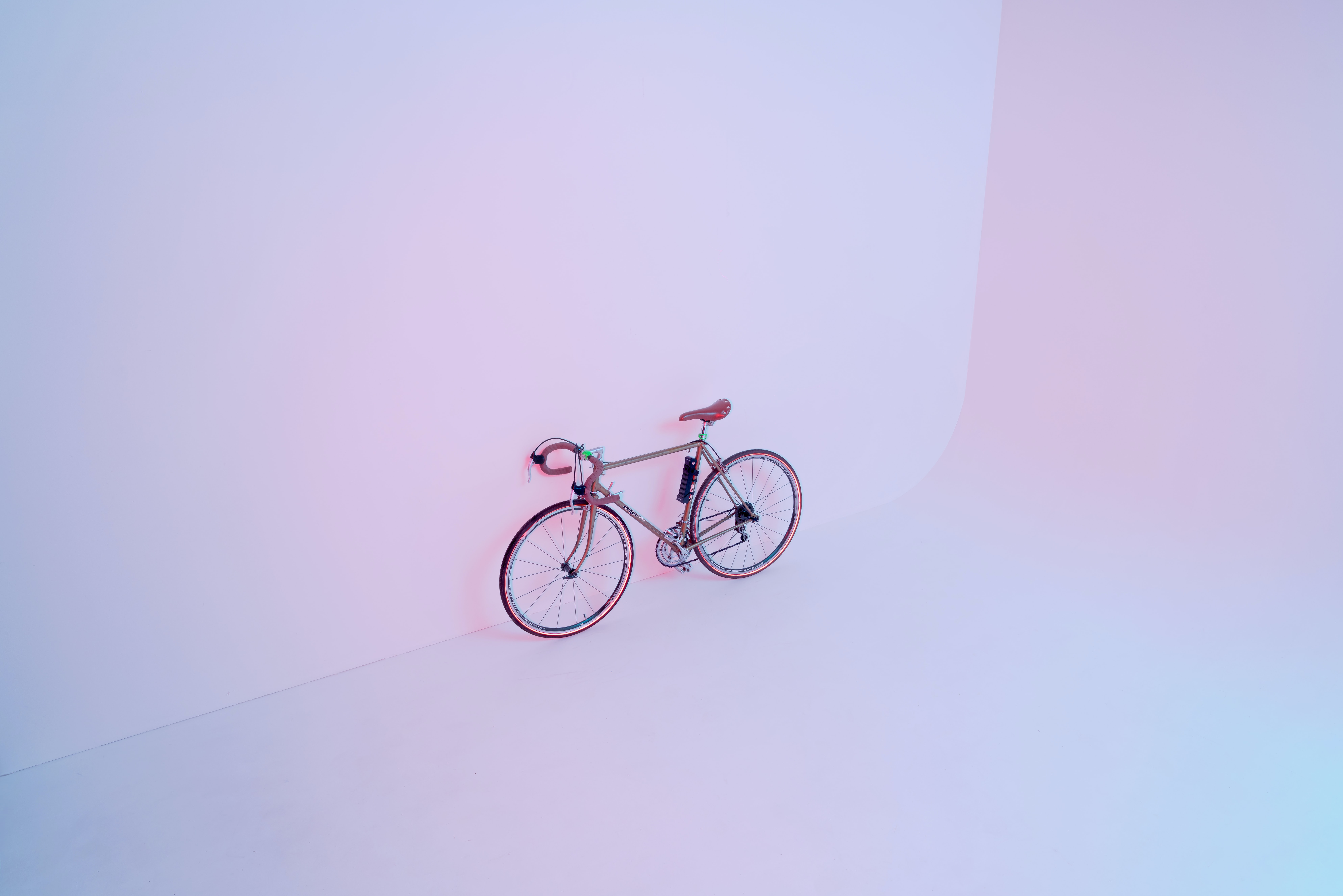 A bicycle leaning against a white wall.
