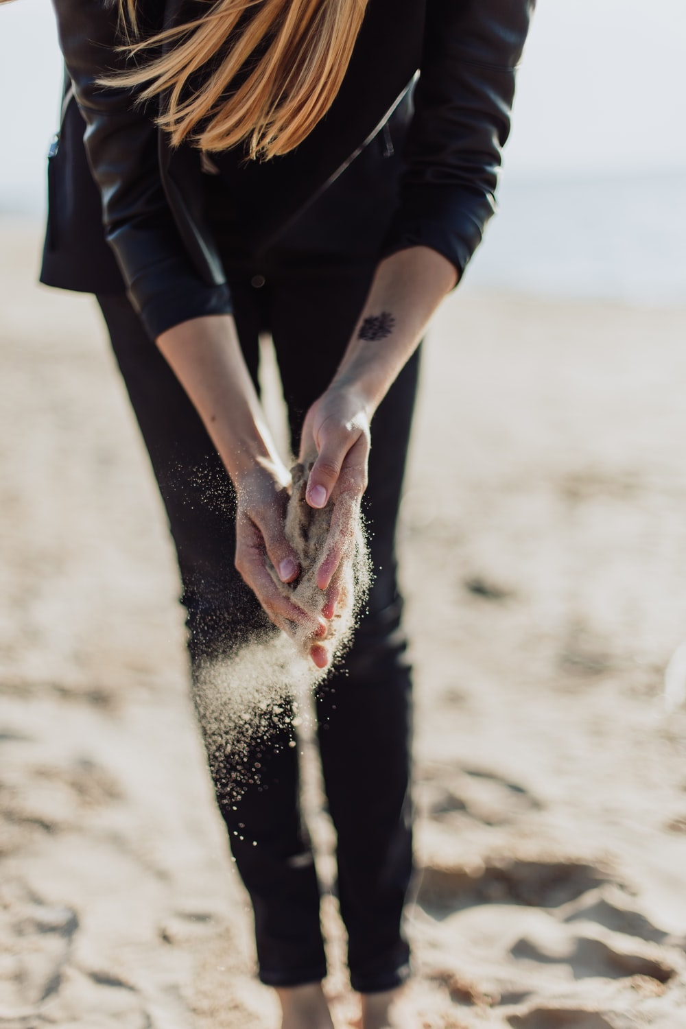 person holding brown sand during daytime