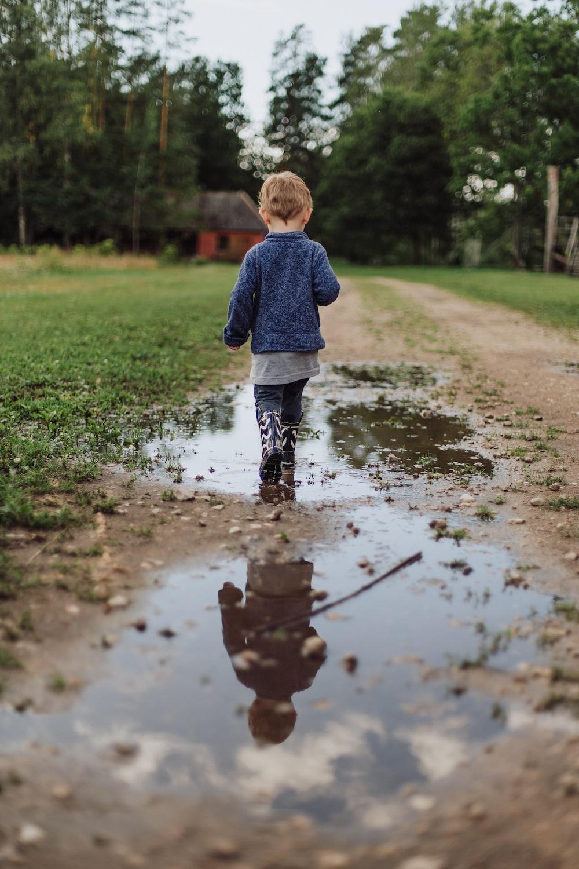 toddler's walking on wet field during daytime