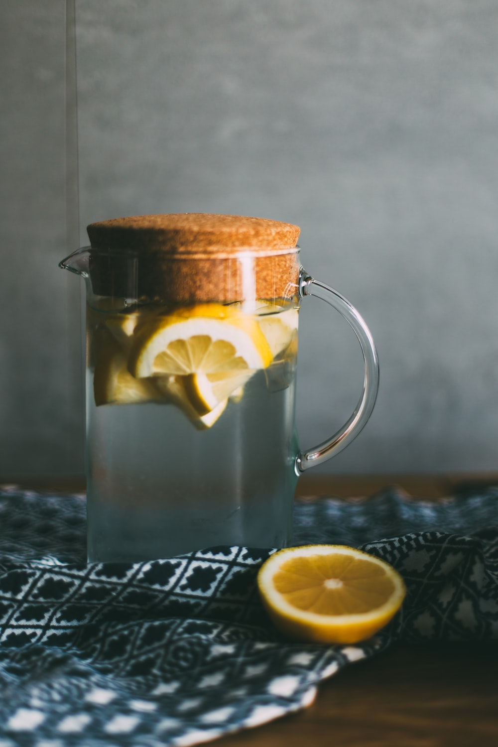 clear glass pitcher filled with sliced lemons on black and white table runner