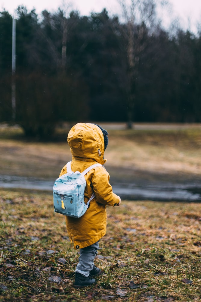Child wearing backpack and jacket wandering outside.