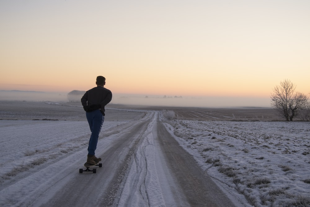man playing skateboard on road