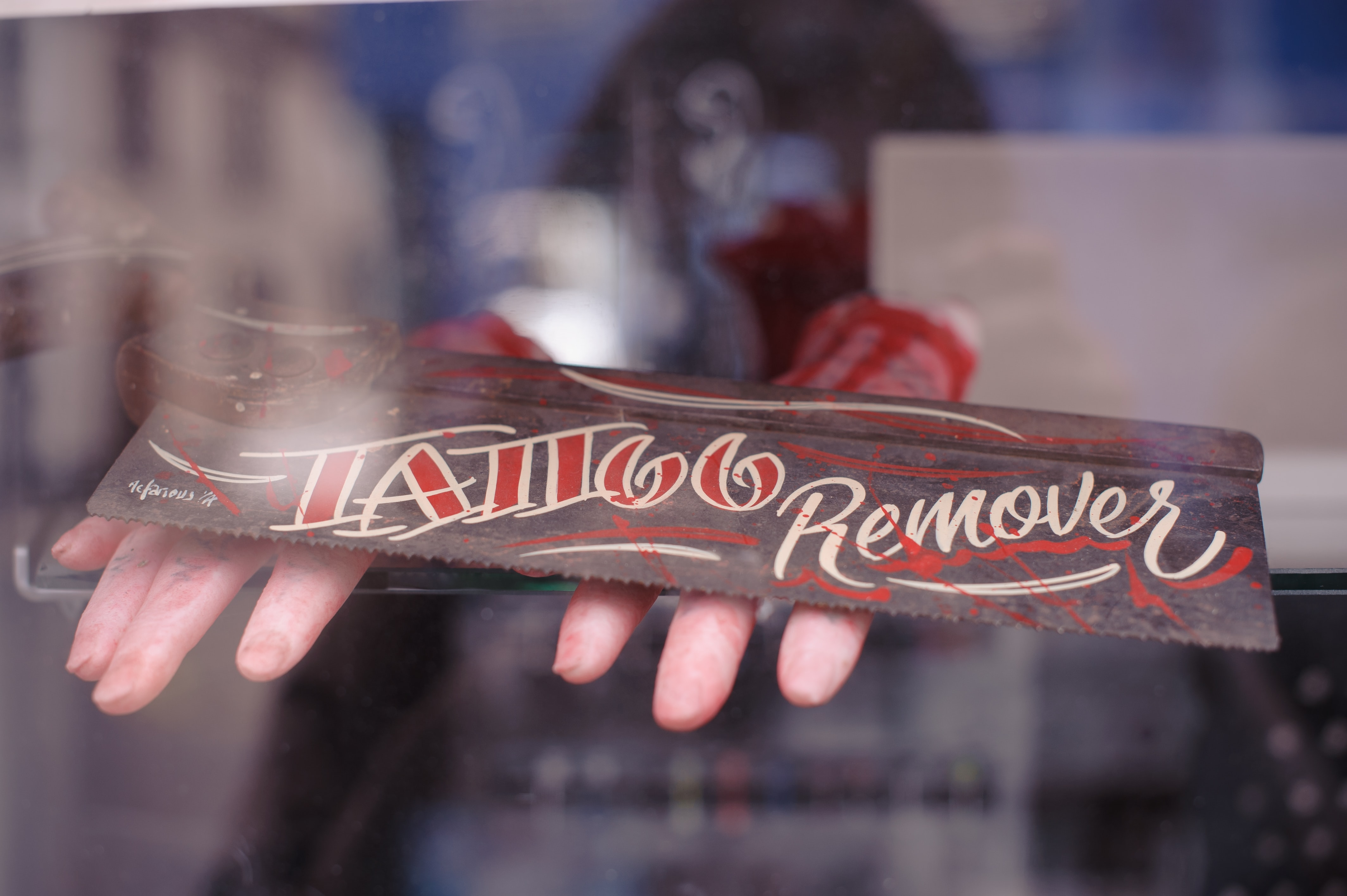 person holding brown wooden Tattoo remover sign
