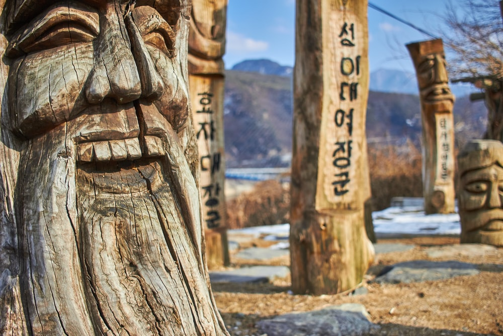 wooden post sculpture face at daytime