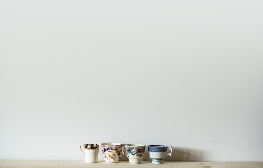 four assorted-color ceramic cups on white table