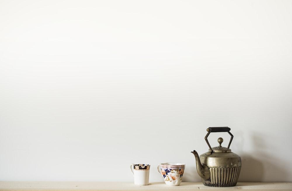 silver kettle beside two mugs