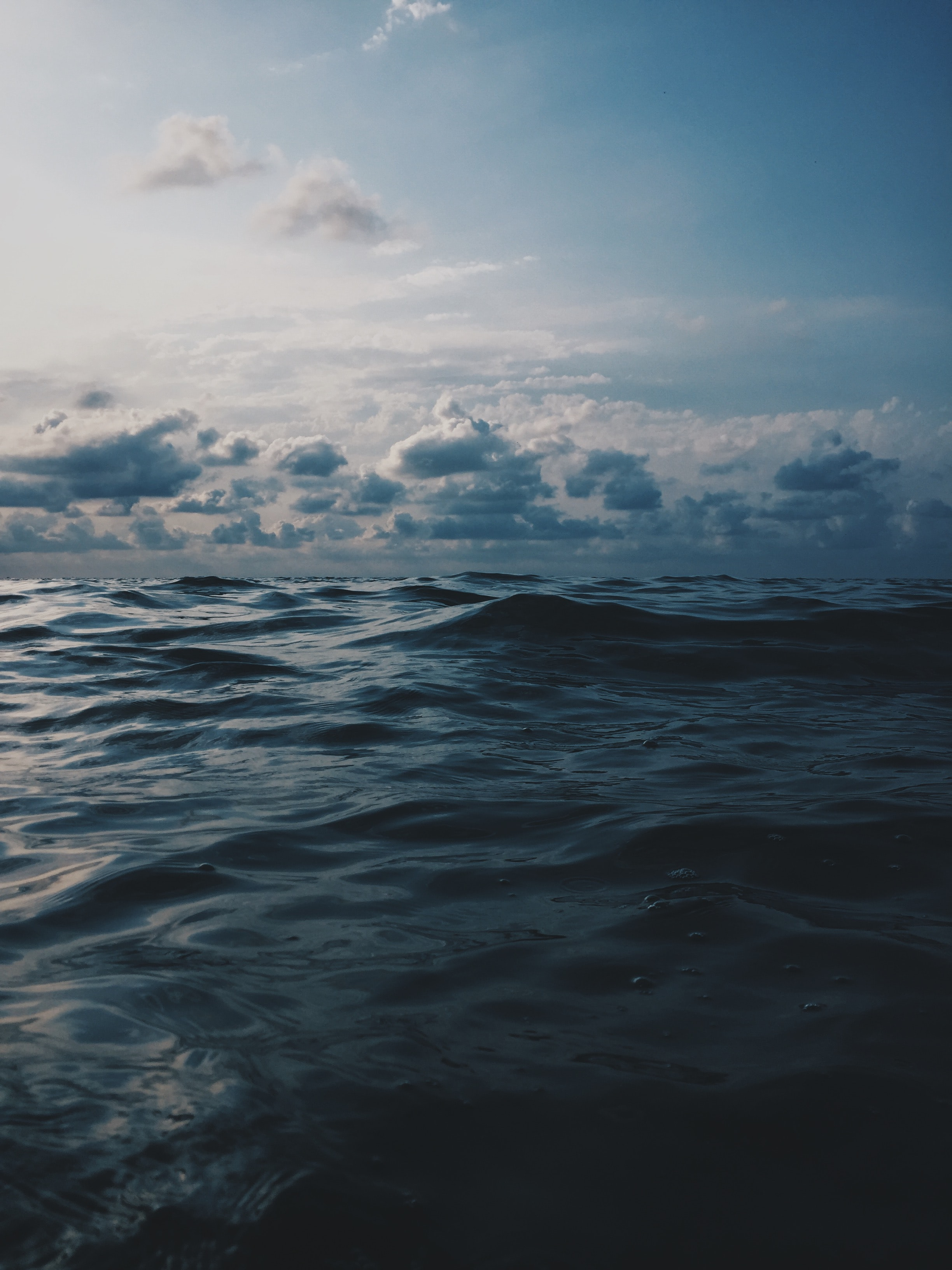 sea under white clouds during daytime