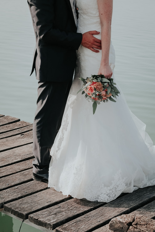 newlywed couple standing on dock