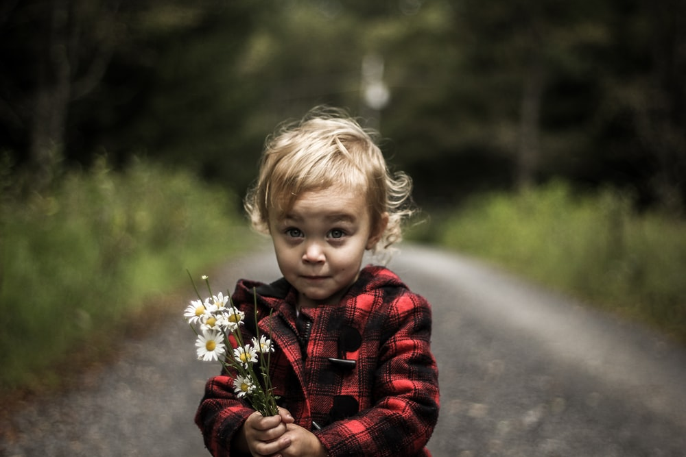 girl wearing red and black plaid jacket holding flower