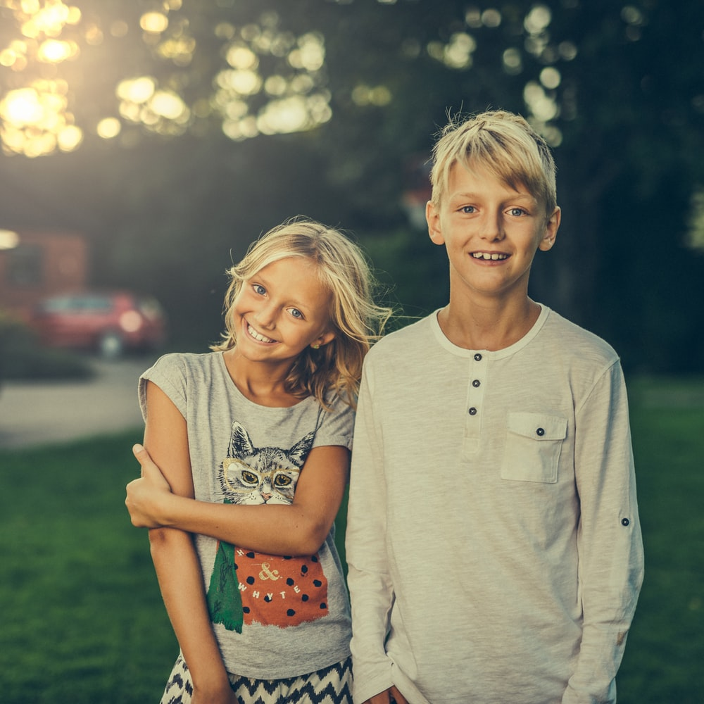 girl and boy standing on green grass field
