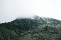 green mountain covered with thick fog