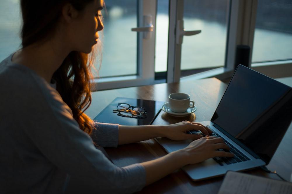 A woman working at a laptop near a half-open window