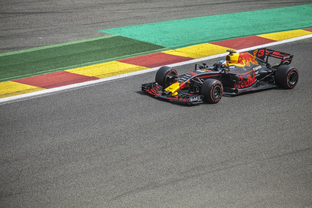black and yellow Red Bull F1 racing in concrete track