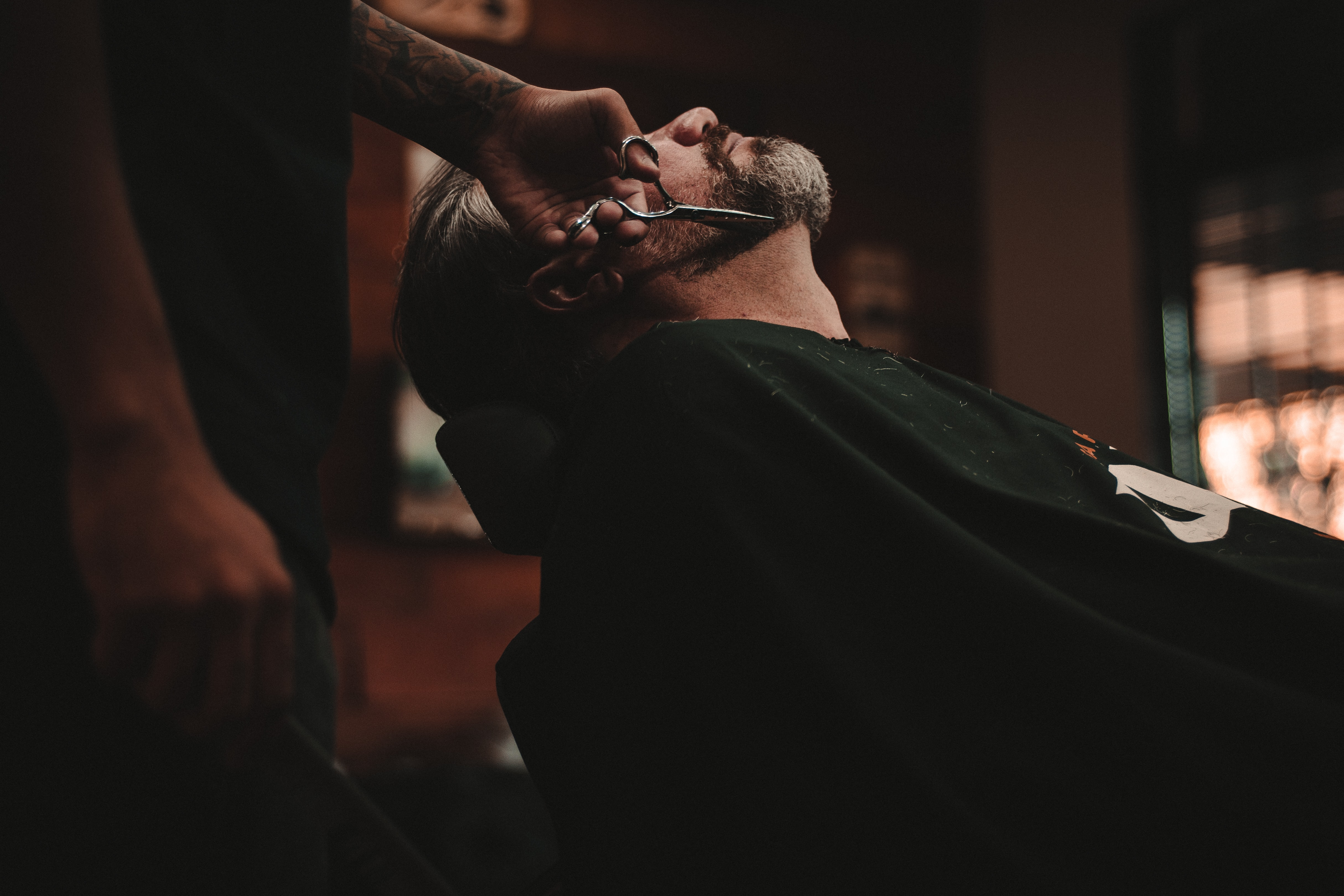 A man getting his beard trimmed at a barbershop in Cianorte
