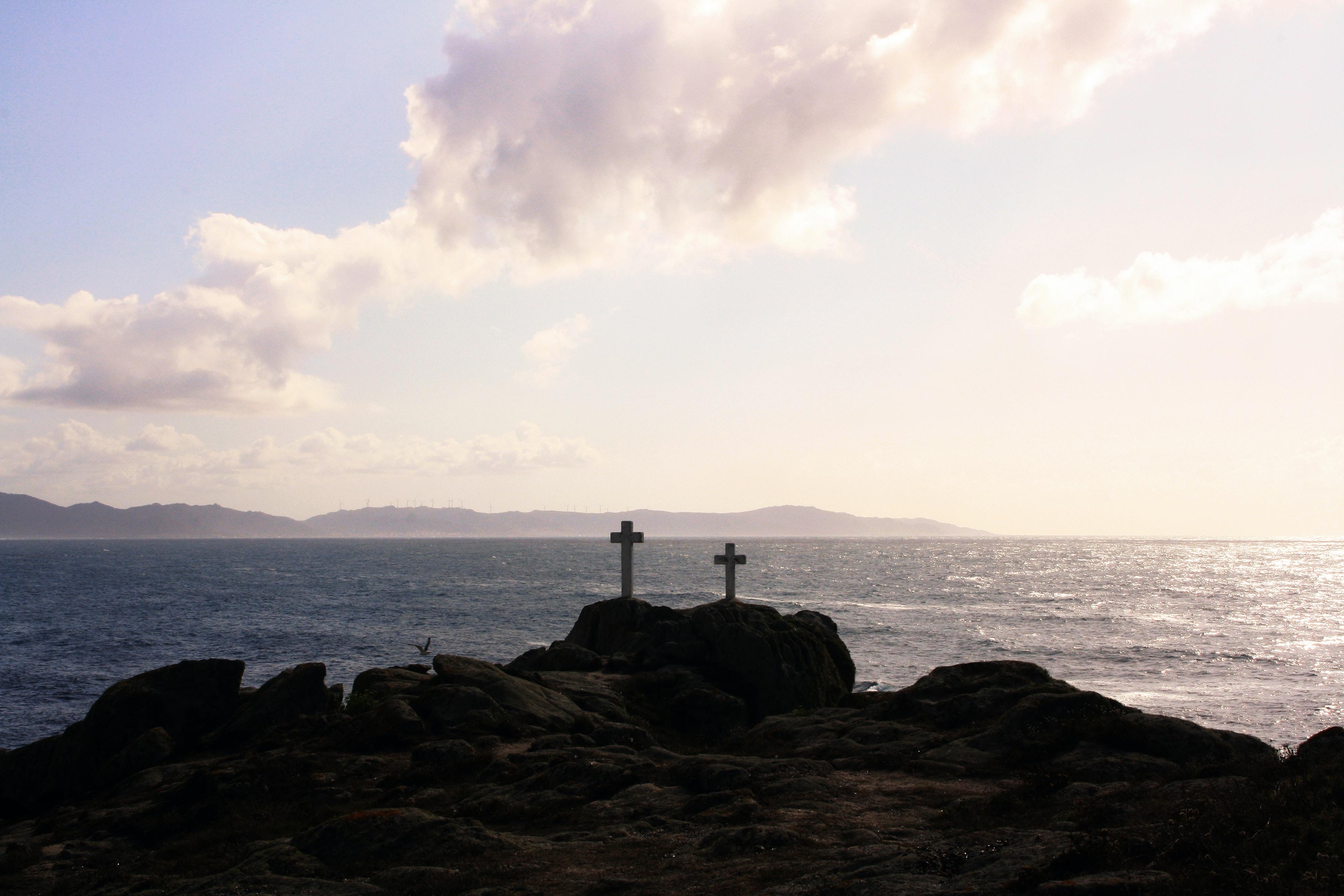 Two little wooden crosses sitting on top of a rock cliff near an ocean.