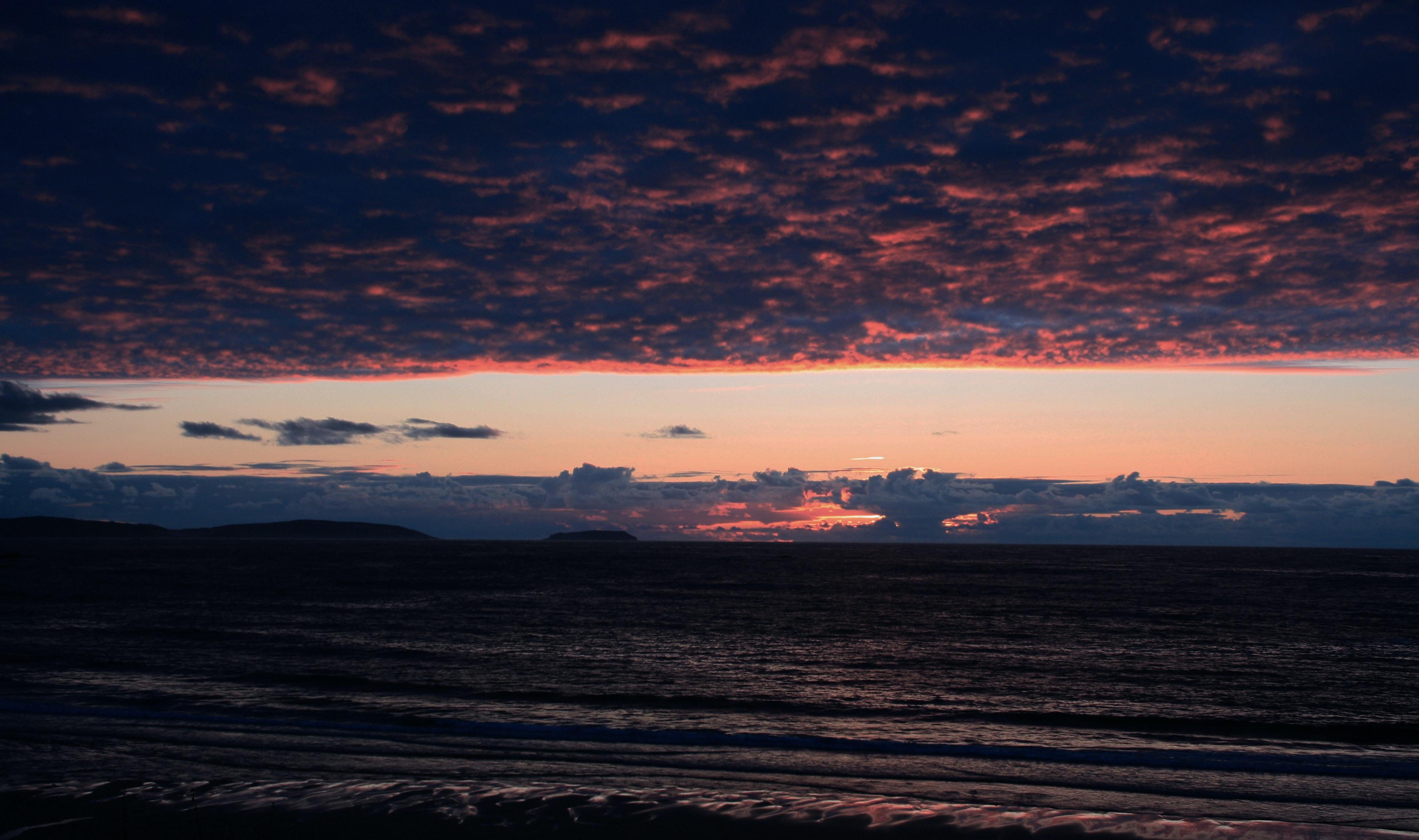 A purple cloud covered sky above a beach.