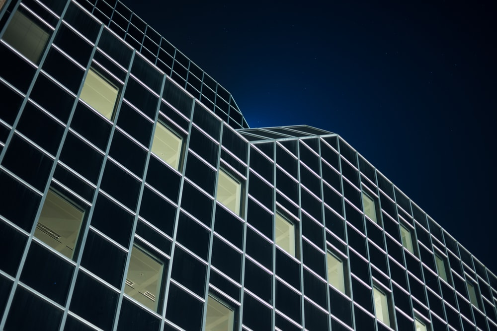 low angle photography of black building during night