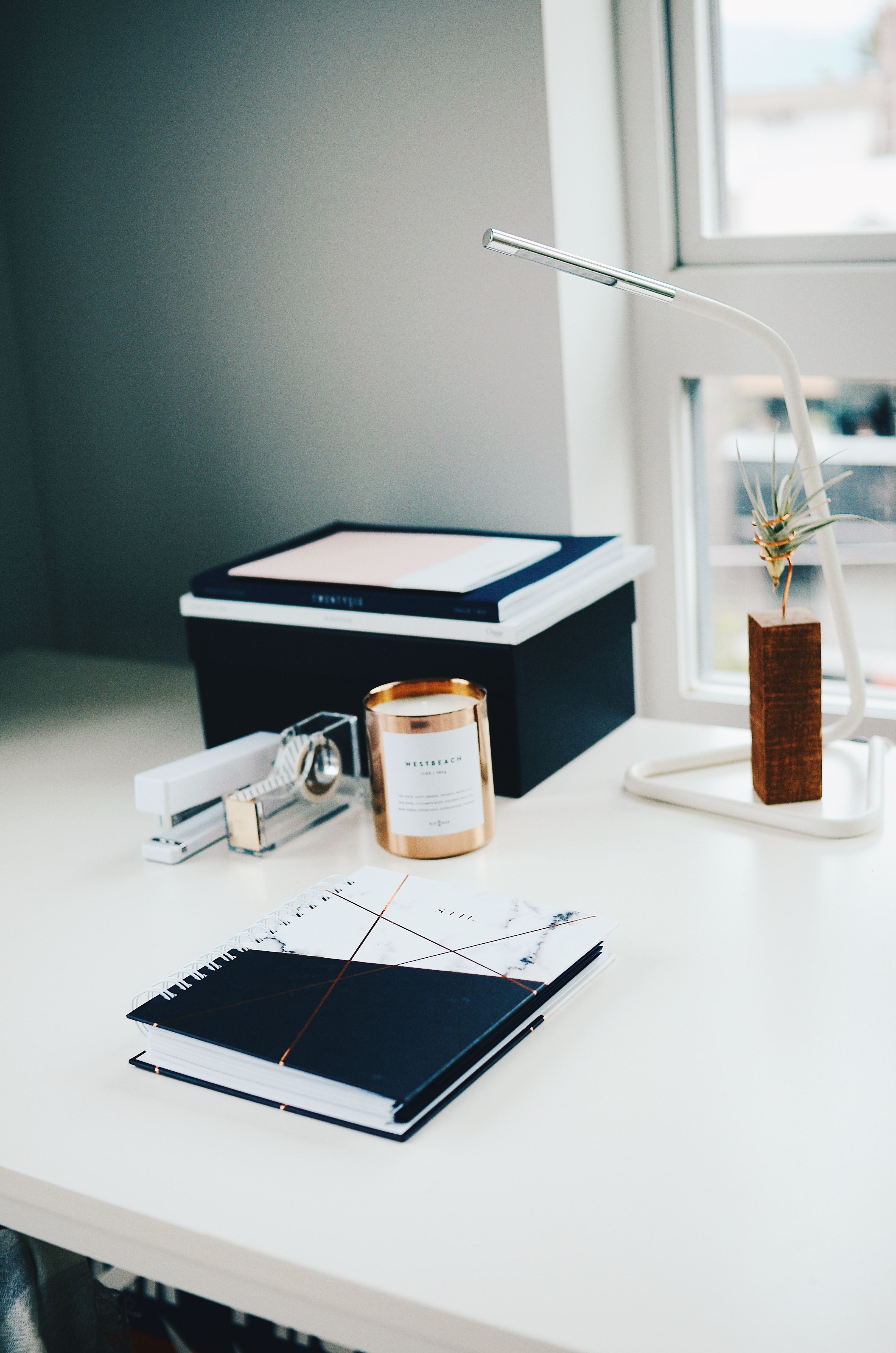 White deskspace with candle, lamp, notebook, stapler and tape dispenser
