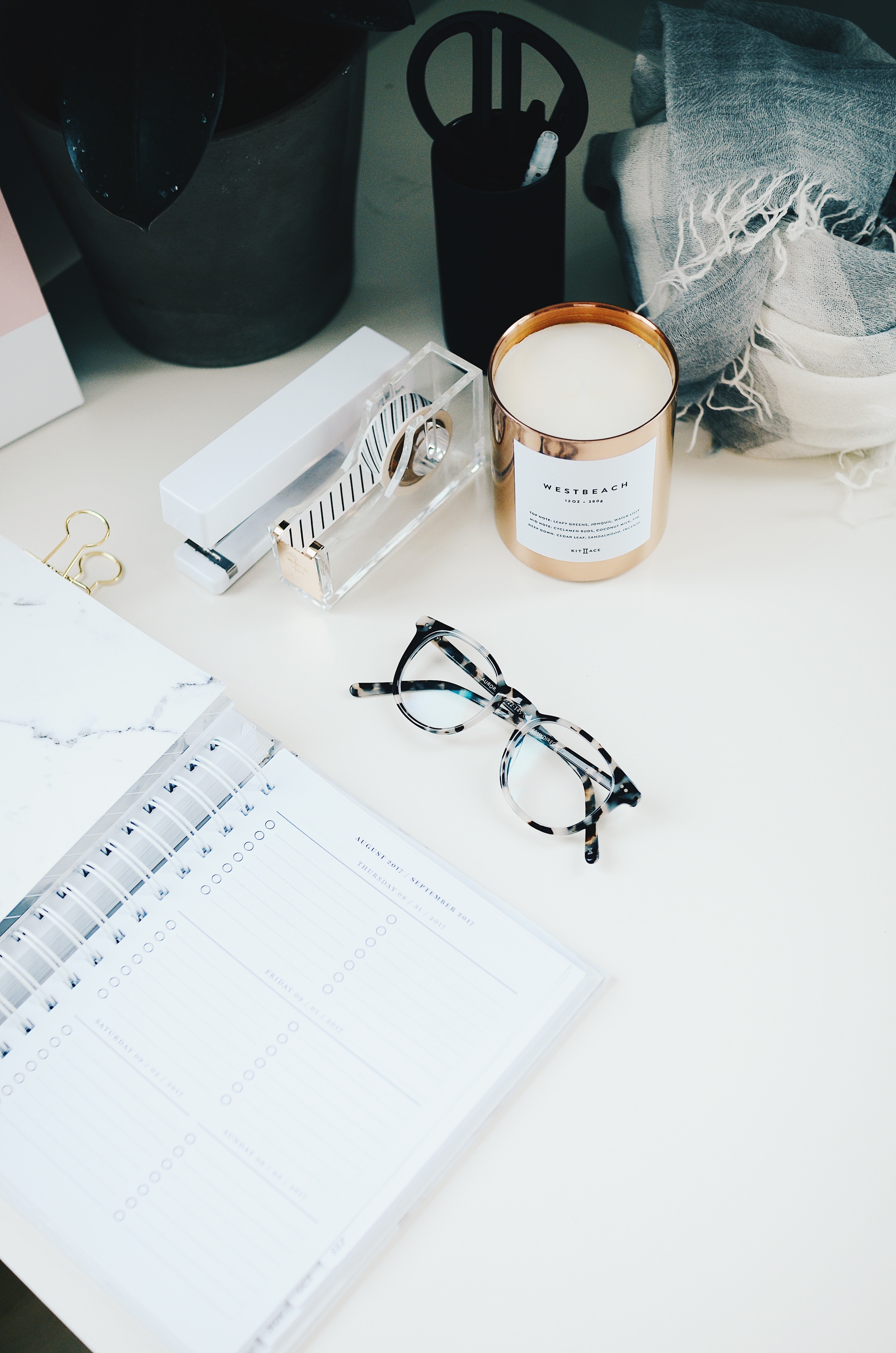 A pair of glasses next to an open planner and a scented candle on a white surface