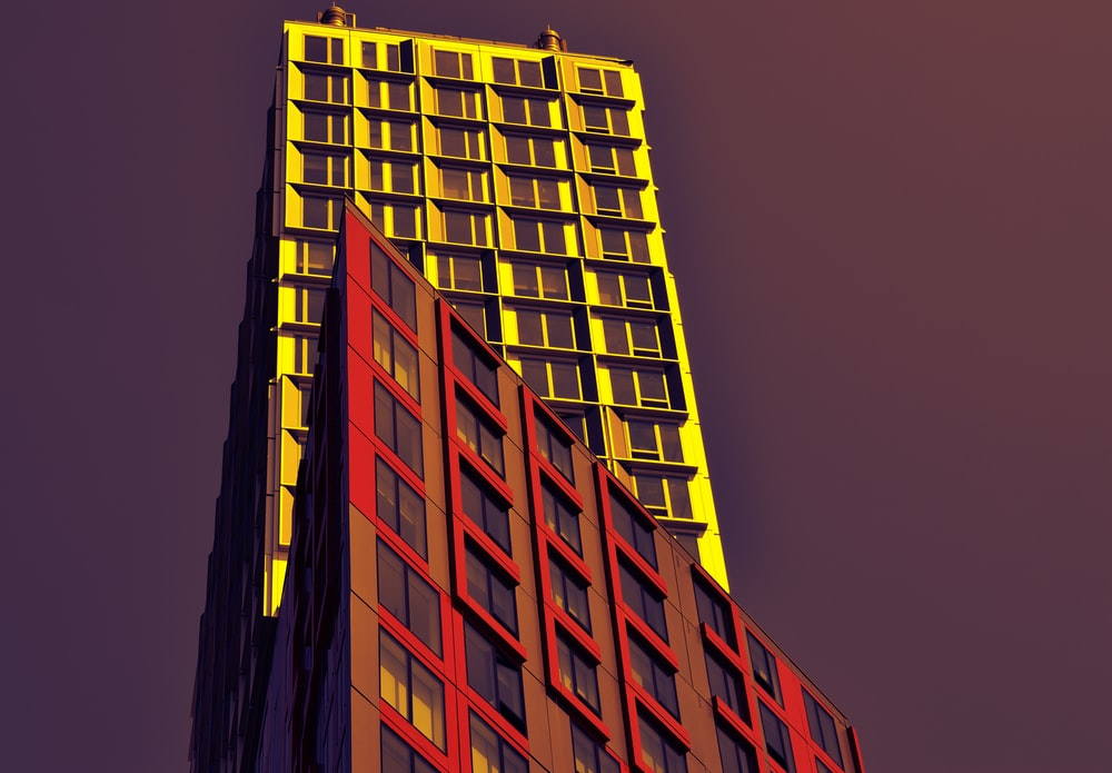 low angle photo of red and yellow high-rise buildings