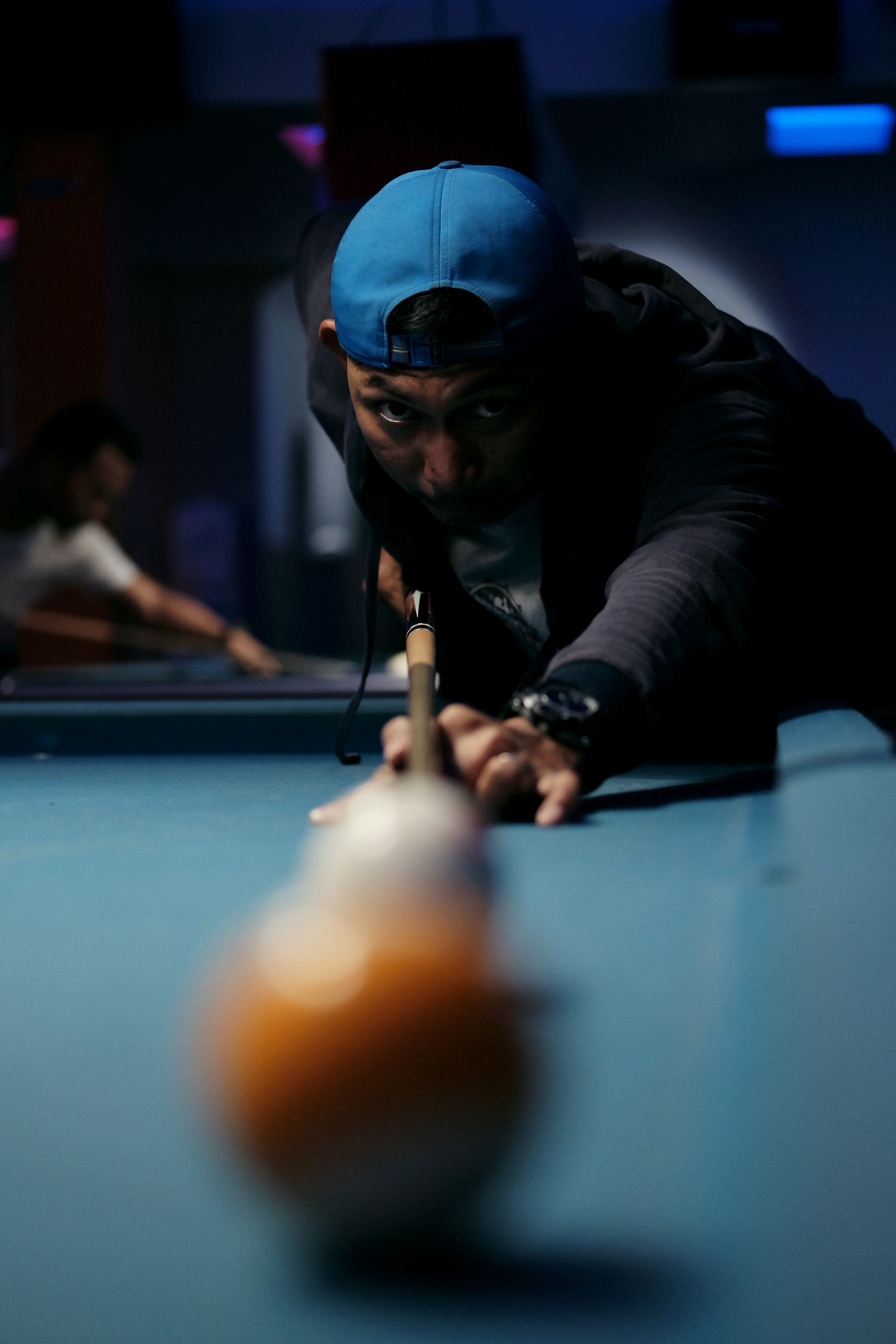 A man with a hat on playing pool.
