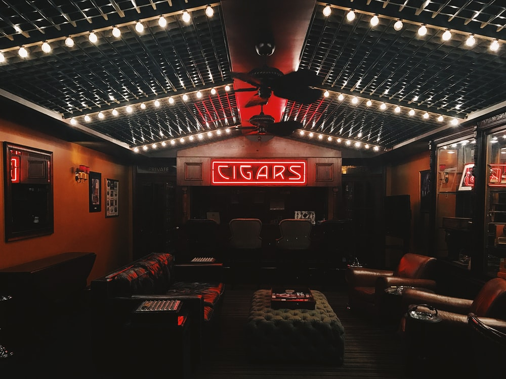 red cigars neon signage in the middle of brown room