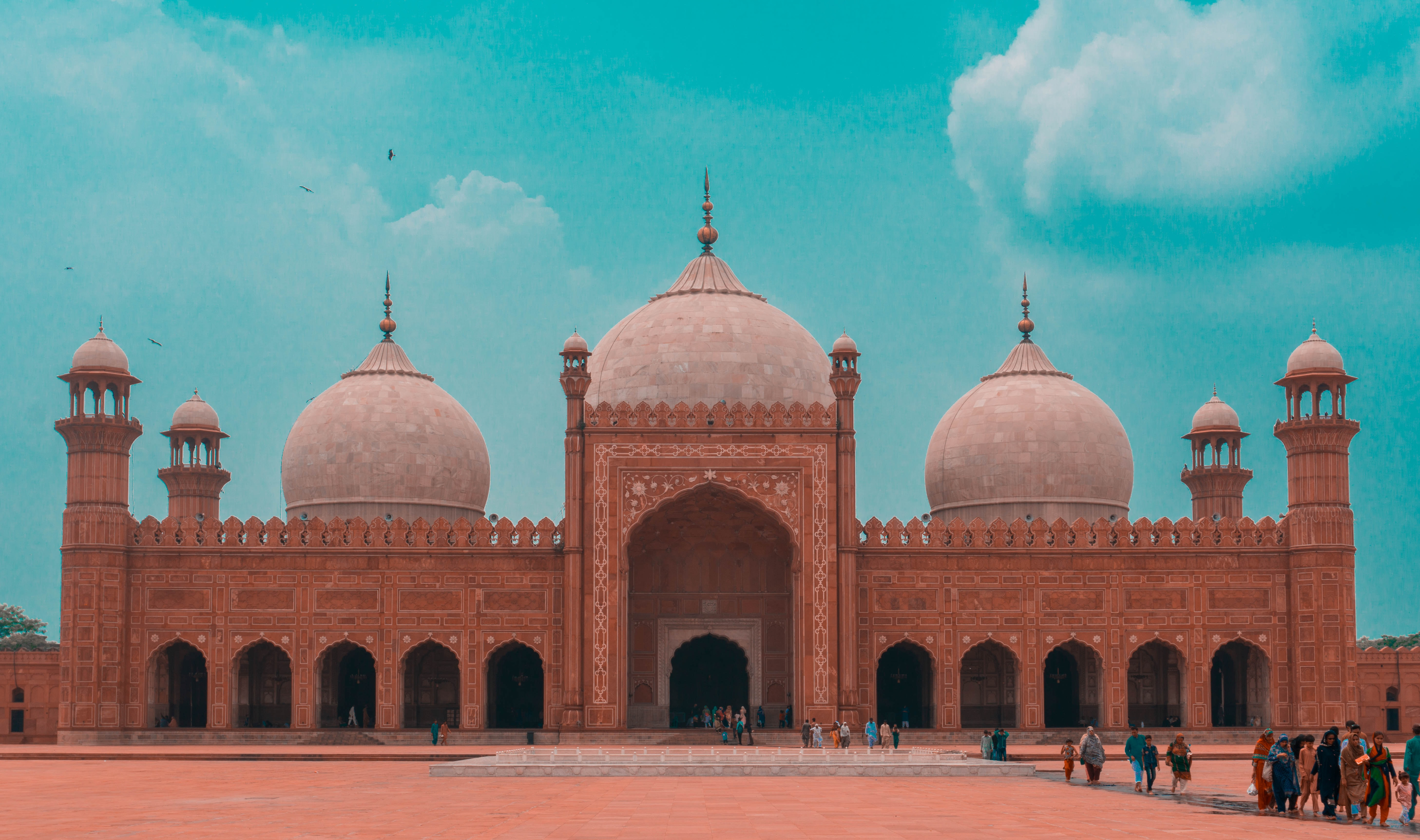 Tourists explore the ornate Badshahi Mosque on a bright blue day