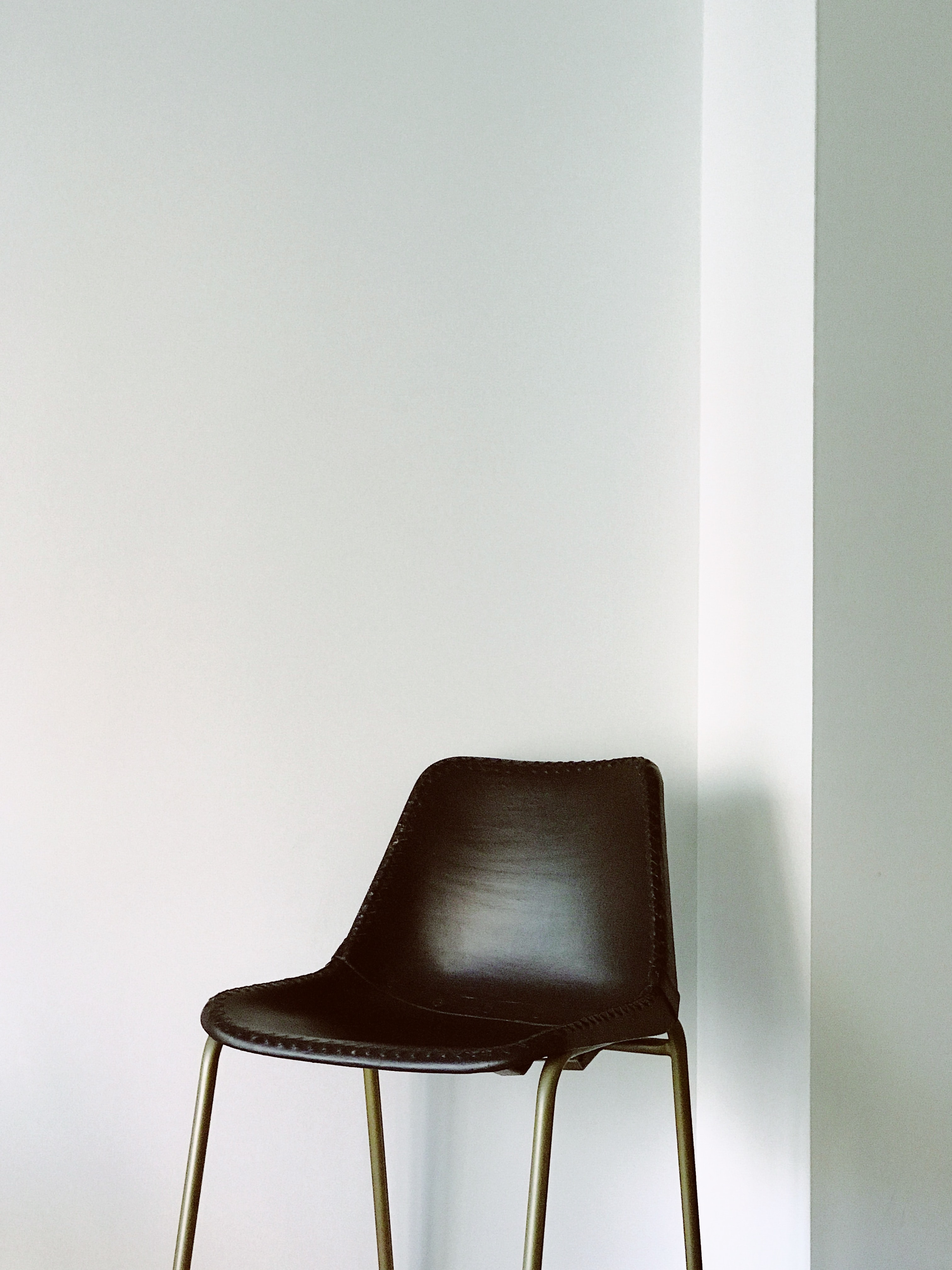 brown chair near white painted wall
