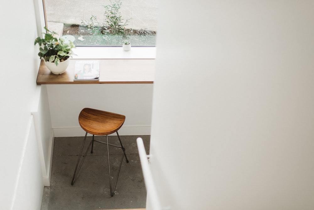brown stool below brown tabletop with green plant in white pot
