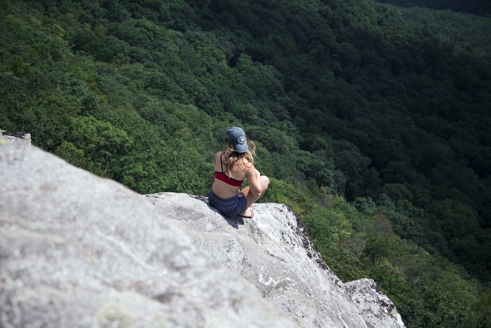 woman sitting in gray rock formation