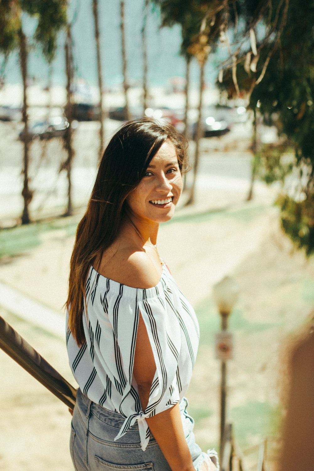 smiling woman standing beside handrails during daytime