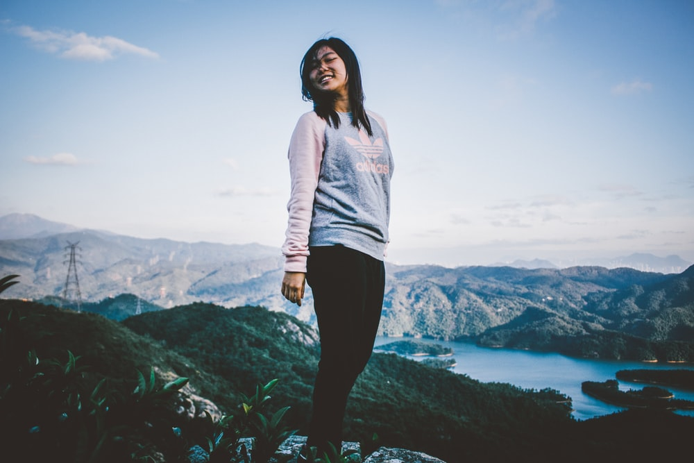 woman standing at the peak of mountain