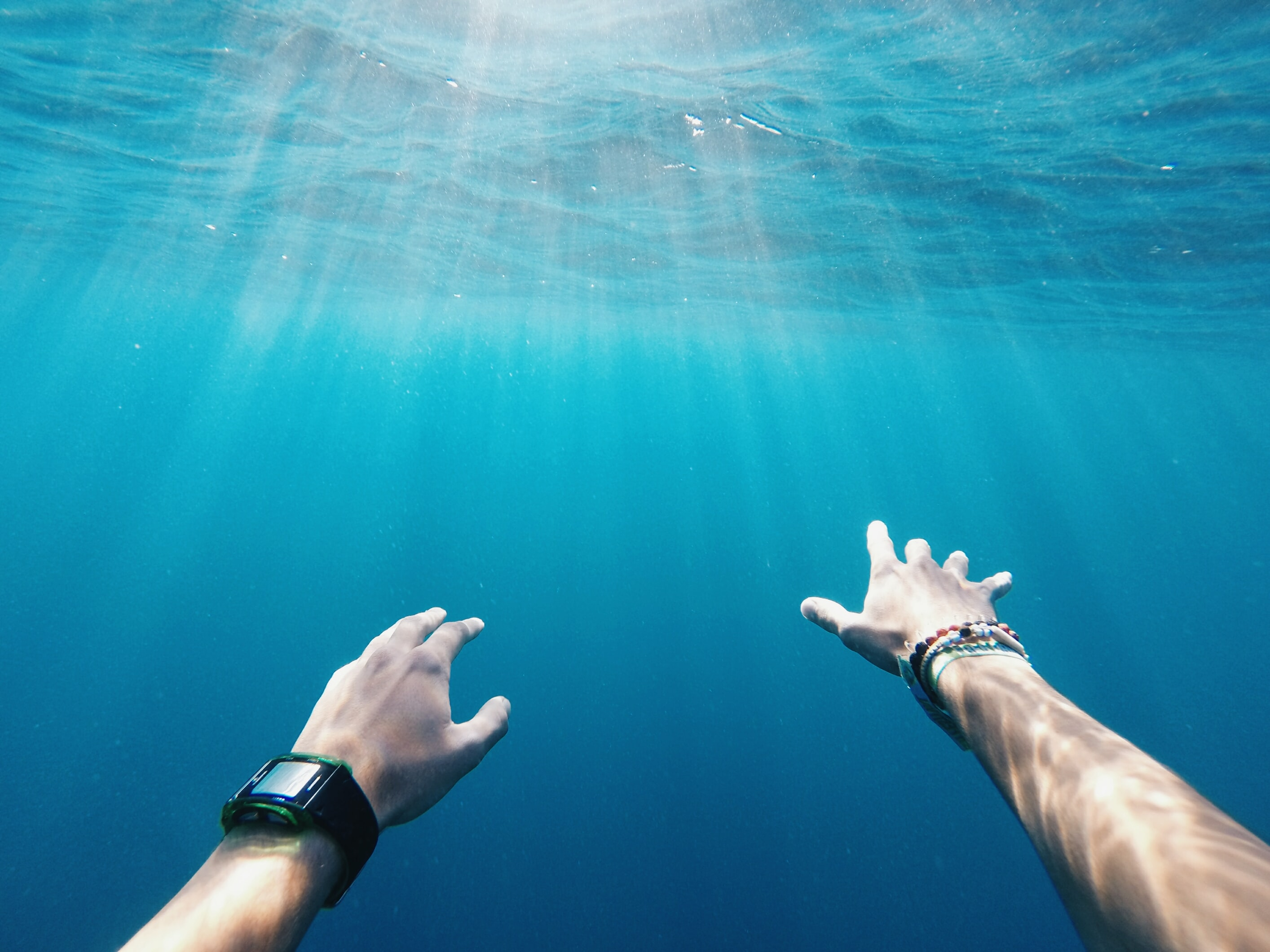 A person wearing a smartwatch reaching out underwater.