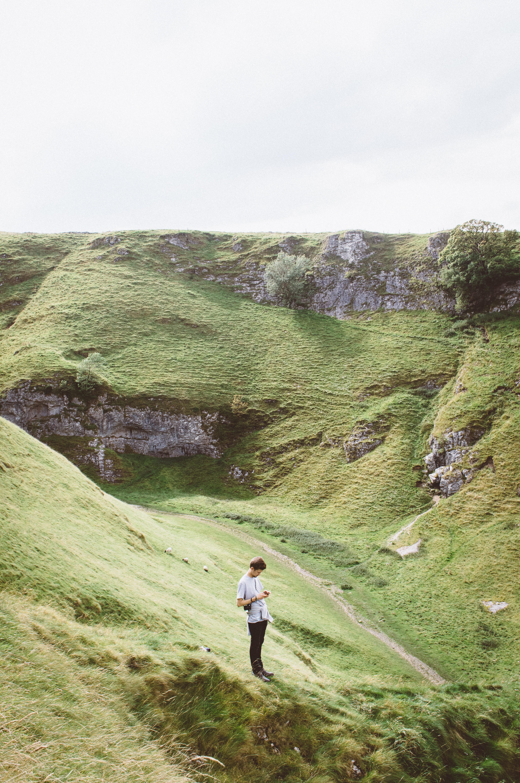 man standing on green grass on mountain