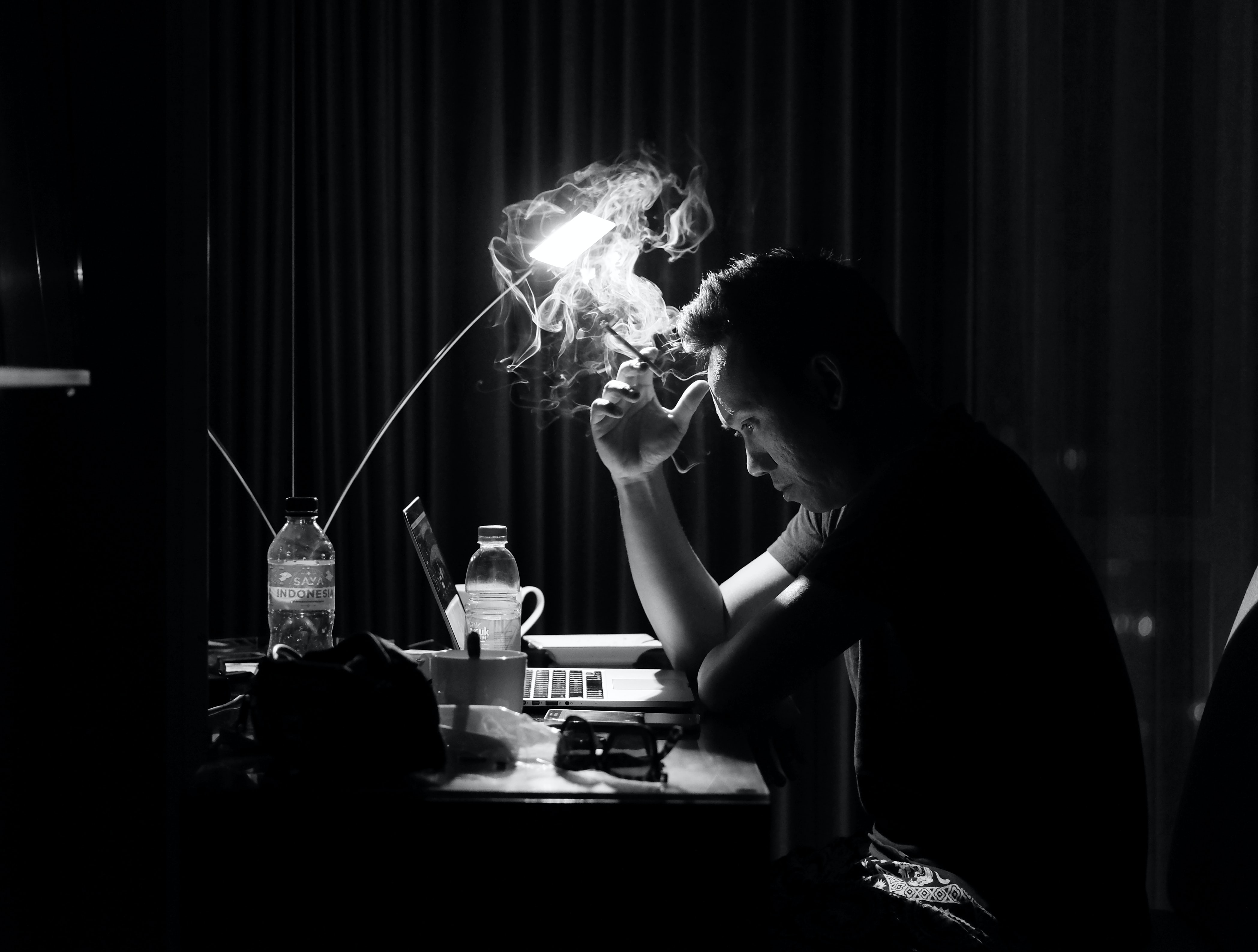 A man sitting at his desk, staring at his computer, smoking a cigarette