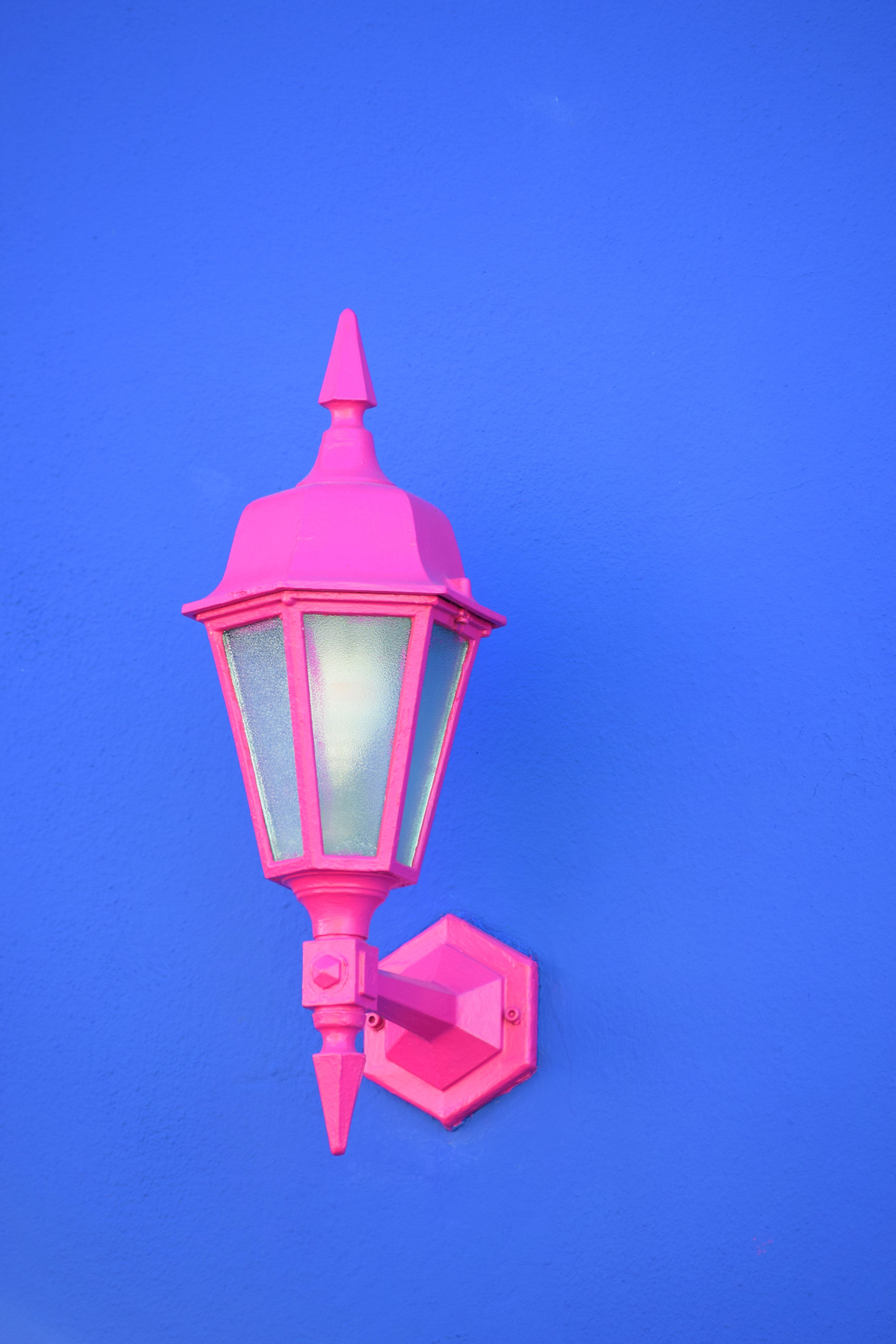 A pink outdoor light attached to a blue wall.