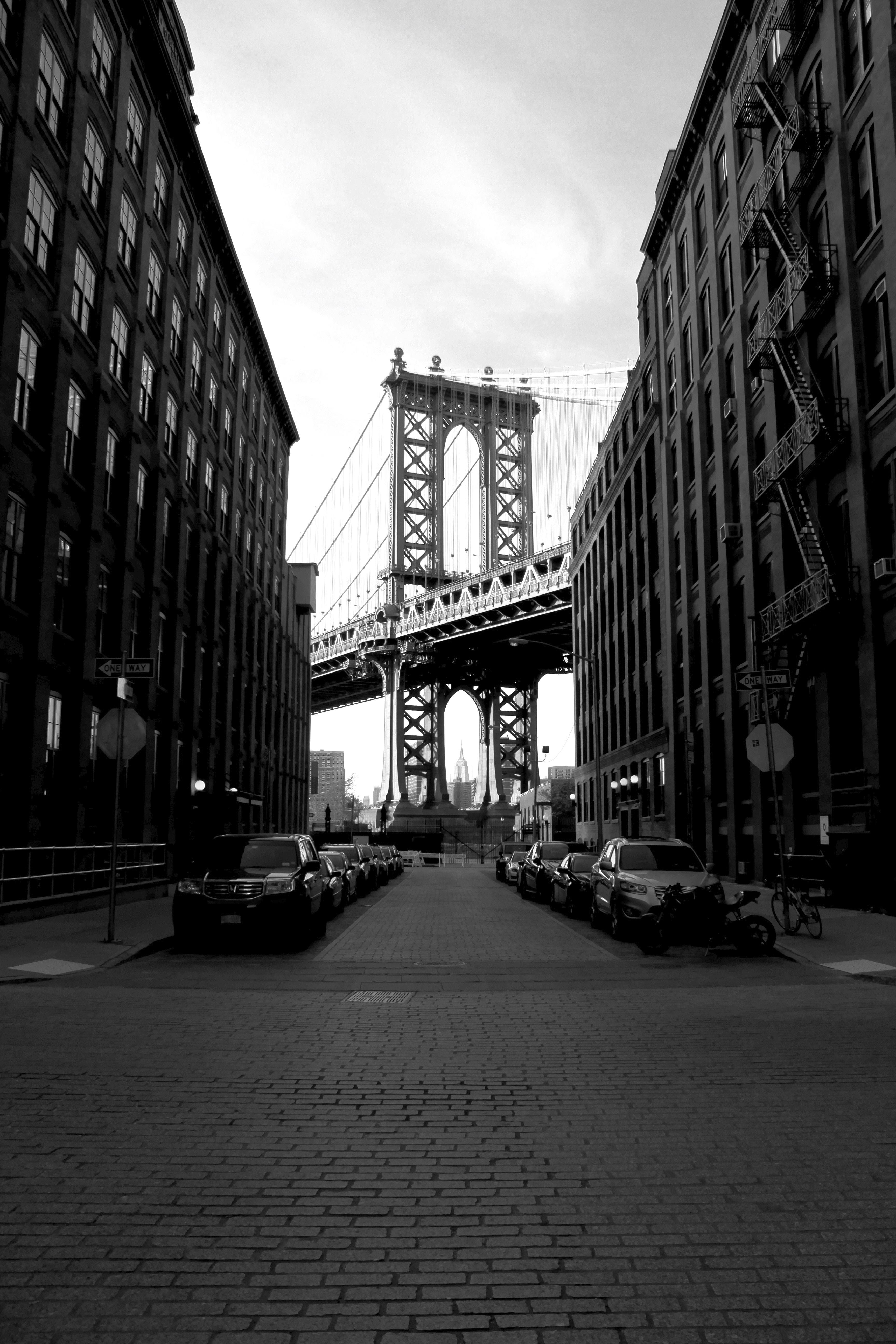 A view down a white street staring at a suspension bridge.