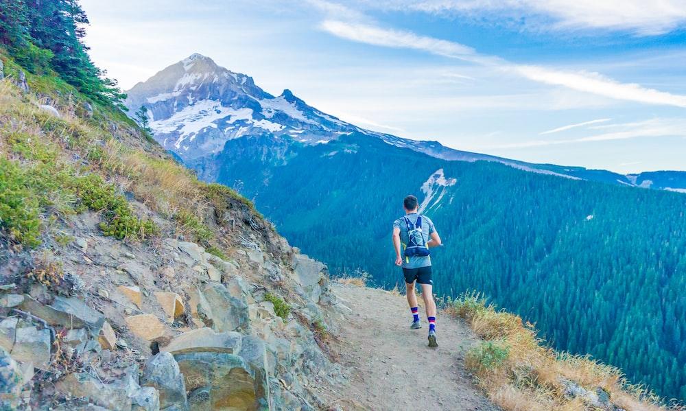 man running on edge near mountain