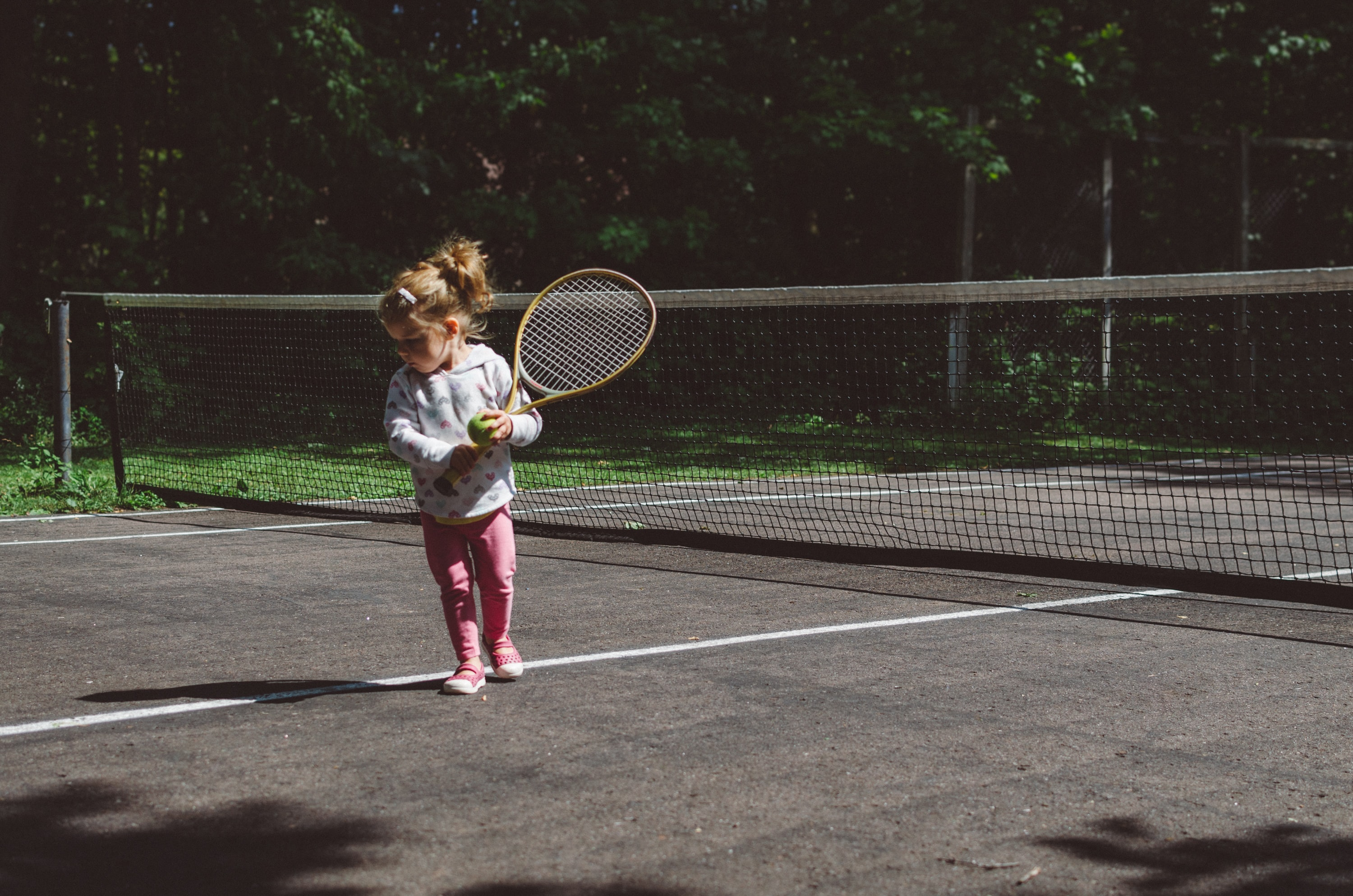 girl holding lawn tennis racket while standing beside white and black net