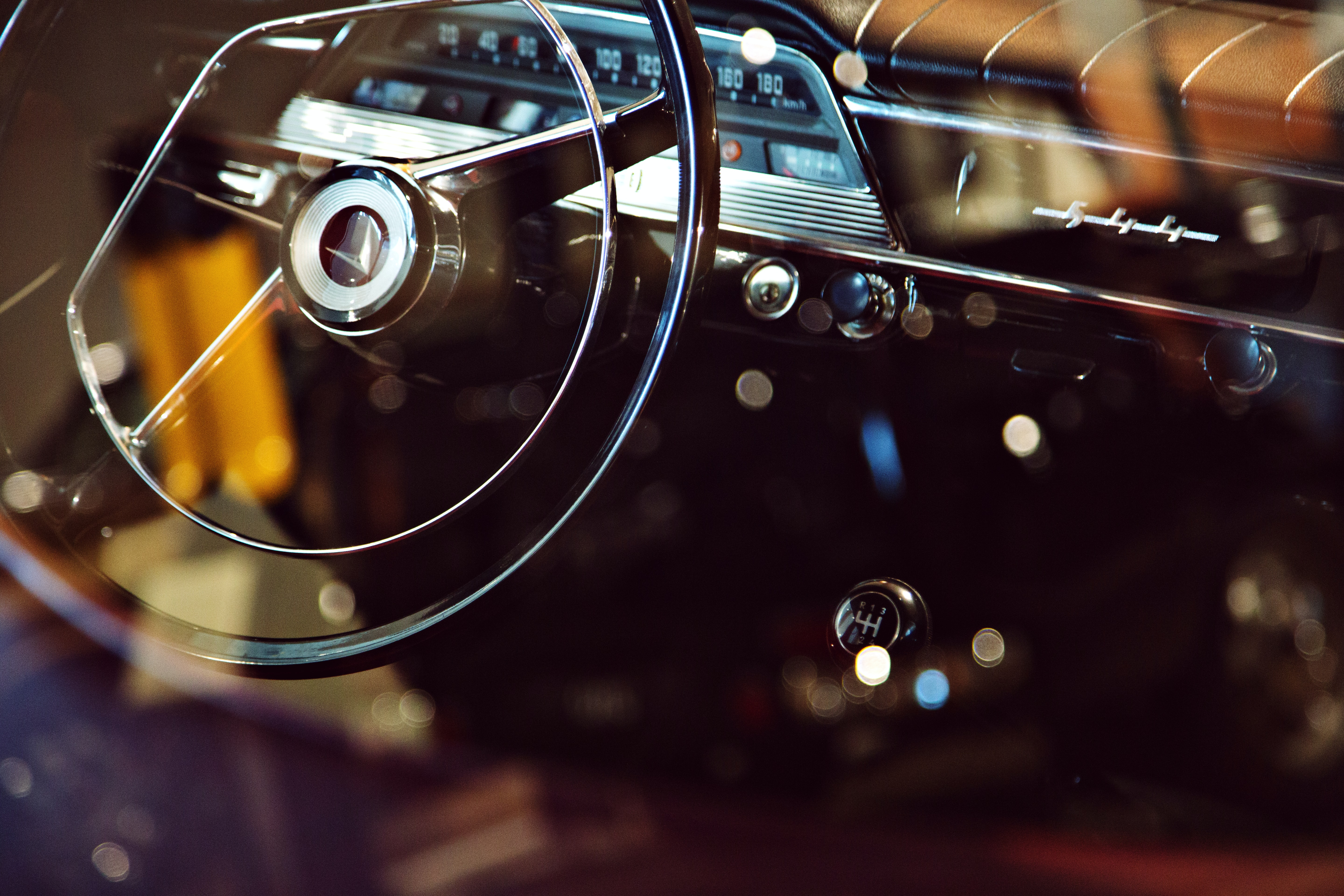 bokeh photography of vehicle steering wheel and gear shift lever